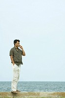 Man standing using cell phone, ocean in background