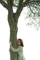 Woman hugging tree, smiling at camera, portrait
