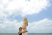 Girl hugging mother, ocean horizon and sky in background