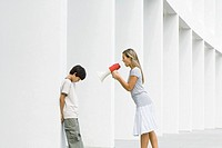 Woman shouting at boy through megaphone, boy lowering head