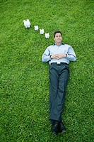 Man lying on grass with eyes closed, piggy banks next to head