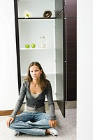 Teenage girl sitting on floor in front of sparse pantry (thumbnail)