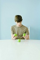 Teen boy holding up comparing three apples (thumbnail)