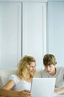 Woman and teenage son using laptop together