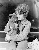 Woman holding puppy All persons depicted are not longer living and no estate exists Supplier warranties that there will be no model release issues
