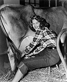 Woman in a barn milking a cow All persons depicted are not longer living and no estate exists Supplier warranties that there will be no model release ...