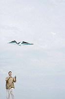 Man flying kite, looking up, three quarter length
