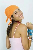 Teenage girl wearing bandana, smiling over shoulder at camera
