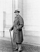 Elegantly dressed man standing in front of a building All persons depicted are not longer living and no estate exists Supplier warranties that there w...