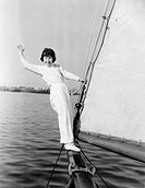 Young girl standing on a sailboat and waving All persons depicted are not longer living and no estate exists Supplier warranties that there will be no...