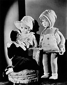 Woman sitting on a chair and looking at two oversized dolls All persons depicted are not longer living and no estate exists Supplier warranties that t...