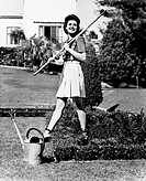 Profile of a young woman carrying a rake on her shoulder in a garden All persons depicted are not longer living and no estate exists Supplier warranti...