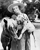 Young woman in a cowboy hat holding a goat while leaning against her pony All persons depicted are not longer living and no estate exists Supplier war...