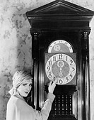 Woman with grandfather clock at midnight All persons depicted are not longer living and no estate exists Supplier warranties that there will be no mod...