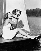 Woman and dog on sailboat All persons depicted are not longer living and no estate exists Supplier warranties that there will be no model release issu...