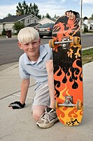 Boy sitting with skateboard, portrait