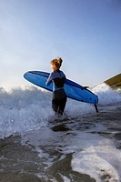 Female surfer running into the surf