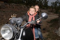 Girls riding an old bike