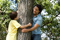 Six year old boy and father hugging tree, Assiniboine Park, Winnipeg, Canada