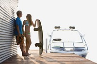 Couple with boat and wakeboarder on dock