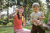 Woman and toddler blowing bubbles