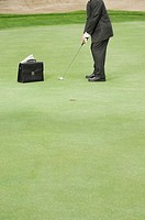 Businessman with briefcase playing golf on golf green