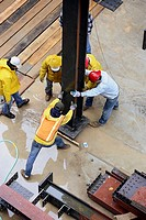 Construction workers erecting steel I beam