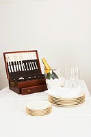 Cutlery box with a champagne bottle and tableware on a dining table