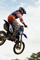 Low angle view of a motocross rider performing a jump on a motorcycle