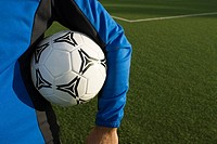 Mid section view of a man holding a soccer ball under his arm