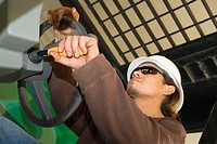 Close-up of a male construction worker holding a steering wheel