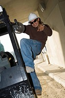 Young man climbing a machine and posing (thumbnail)