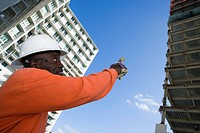 Low angle view of a male construction worker pointing towards the building