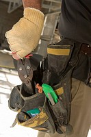 Mid section view of a man putting pliers into a tool belt