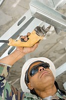 Close-up of a male construction worker working with a hand drill