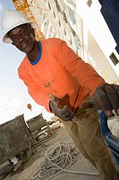 Portrait of a mid adult man pulling a generator cable at a construction site
