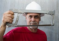 Portrait of a mature man holding a coping saw