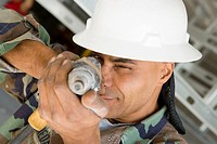 Close-up of a male construction worker aiming with a hand drill