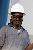Close-up of a mature man with a pair of eyeglasses and a hardhat