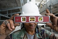 Close-up of a male construction worker holding a level