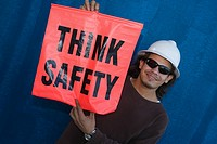 Close-up of a male construction worker smiling and holding a warning sign