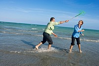 Mid adult man holding a fishing net over a mid adult woman on the beach
