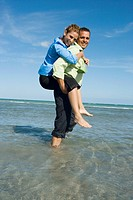 Side profile of a mid adult woman riding piggyback on a mid adult man on the beach (thumbnail)
