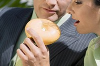 Close-up of a businessman feeding donut to a businesswoman