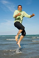 Mid adult man jumping on the beach (thumbnail)