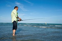 Side profile of a mid adult man fishing in the sea