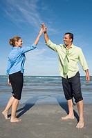 Mid adult couple giving high-five to each other and smiling