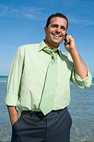 Mid adult man talking on a mobile phone on the beach