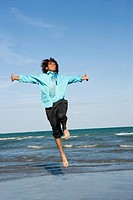 Mid adult man jumping on the beach with his arm outstretched