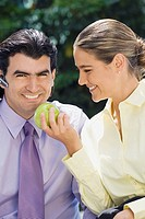 Businesswoman feeding a green apple to a businessman and smiling